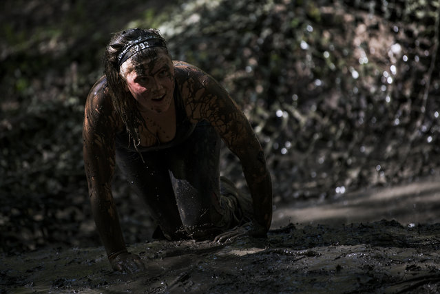 A woman crosses the Dirt Ditch obstacle as she competes during the Tough Viking race on May 12, 2018 in Stockholm. (Photo by Jonathan Nackstrand/AFP Photo)