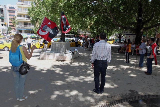 Turks, some of them wearing national flags with images of Turkey's founder Kemal Ataturk, stand in a silent protest in Kugulu Park in Ankara, Turkey, Wednesday, June 19, 2013. After weeks of sometimes-violent confrontation with police, Turkish protesters have found a new form of resistance: standing still and silent. (Photo by Burhan Ozbilic/AP Photo)