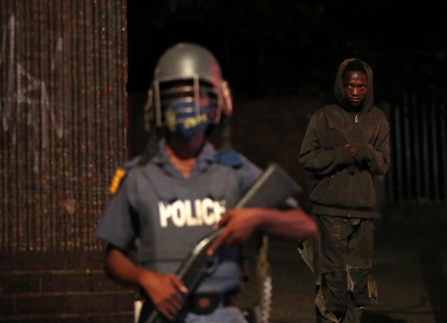 A man looks on as a police officer keeps watch on New Year's day as a nighttime curfew is reimposed amid a nationwide coronavirus disease (COVID-19) lockdown, in Johannesburg, South Africa on January 1, 2021. (Photo by Siphiwe Sibeko/Reuters)