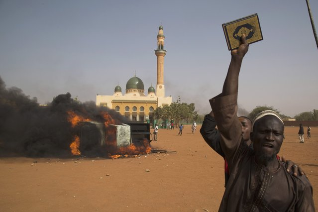 A man holds a copy of the Koran during a protest against Niger President Mahamadou Issoufou's attendance last week at a Paris rally in support of French satirical weekly Charlie Hebdo, which featured a cartoon of the Prophet Mohammad as the cover of its first edition since an attack by Islamist gunmen, in Niamey January 17, 2015. (Photo by Tagaza Djibo/Reuters)