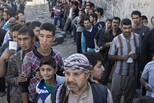 People queue to receive aid packages in Gogjali, on the eastern edge of Mosul, Iraq, Thursday, November 3, 2016. (Photo by Marko Drobnjakovic/AP Photo)