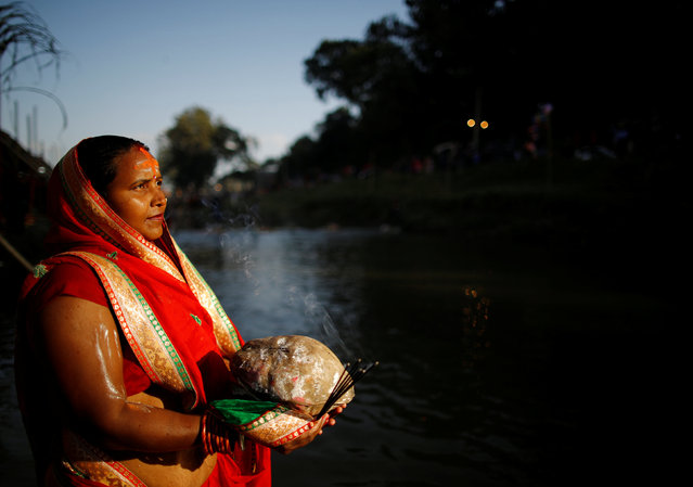 """Light illuminates a devotee as she offers prayers to the setting sun during the """"Chhat"""" festival at Bagmati River in Kathmandu, Nepal November 6, 2016. Chhath is an ancient Hindu Vedic festival historically native to eastern Uttar Pradesh, North Bihar of India and Mithila State of Nepal. The Chhath Puja is dedicated to the Sun and his wife Usha in order to thank them for bestowing the bounties of life on earth and to request the granting of certain wishes. This festival is observed by Nepalese people and Indian people, along with their diaspora. The rituals of the festival are rigorous and are observed over a period of four days. They include holy bathing, fasting and abstaining from drinking water (Barta), standing in water for long periods of time, and offering prashad (prayer offerings) and arghya to the setting and rising sun. (Photo by Navesh Chitrakar/Reuters)"""