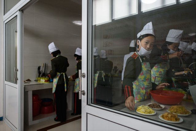 In this photo taken on June 15, 2018 female students take part in cooking lessons at the Kang Pan Sok military academy in Pyongyang. Donald Trump dangled the carrot of foreign investment in front of North Korean leader Kim Jong Un at their nuclear summit, but analysts say few will want to put money into one of the highest-risk business environments in the world. (Photo by Ed Jones/AFP Photo)