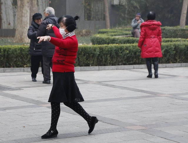 "A woman wearing a mask dances at a park amid heavy smog after the city issued its first ever ""red alert"" for air pollution, in Beijing, China, December 8, 2015. (Photo by Kim Kyung-Hoon/Reuters)"
