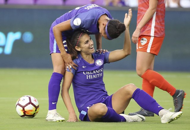 Orlando Prides's Kristen Edmonds, top, talks with Alex Morgan during an NWSL soccer match against the Houston Dash on Wednesday, June 27, 2018, in Orlando, Fla. (Photo by Stephen M. Dowell/Orlando Sentinel via AP Photo)
