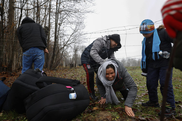 Malika from Afghanistan is helped by her husband Ahmed to crawl under a fence a few kilometers from the Bosnia-Croatia border near Velika Kladusa in Bosnia Wednesday December 9, 2020. Entire migrant families are on the move in cold weather in Bosnia while trying to reach the West as the European Union warns the Balkan country it must act to prevent a humanitarian disaster. A statement by the EU Bosnia mission says current weather conditions are putting at risk the lives of more than 3,000 people sleeping rough or staying in inadequate conditions. (Photo by Marc Sanye/AP Photo)