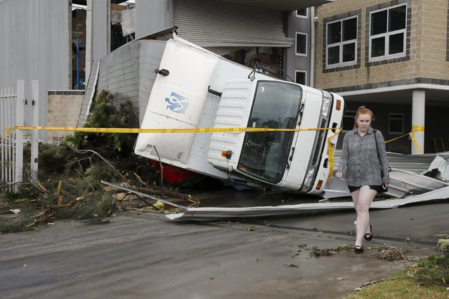 A truck lays overturned onto a car following strong winds at a Kurnell industrial park after a rare tornado hit the Sydney suburb December 16, 2015. (Photo by Jason Reed/Reuters)