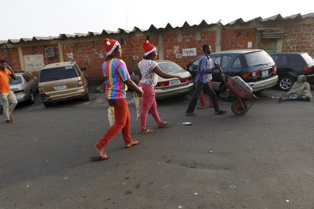 Christmas shoppers leave with shopping bags after shopping on the eve of Christmas at Wuse market in Abuja, Nigeria December 24, 2015. (Photo by Afolabi Sotunde/Reuters)