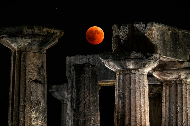 "A picture shows the full moon during a ""blood moon"" eclipse over the temple of Apollo in Corinth on July 27, 2018. The longest ""blood moon"" eclipse this century began on July 27, coinciding with Mars' closest approach in 15 years to treat skygazers across the globe to a thrilling celestial spectacle. (Photo by Valerie Gache/AFP Photo)"