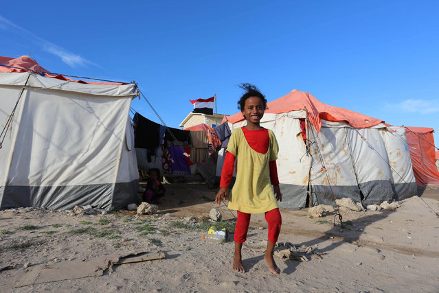 A Yemeni refugee girl walks from their shelter tent at a makeshift camp in Somalia's capital Mogadishu, December 16, 2015. (Photo by Feisal Omar/Reuters)