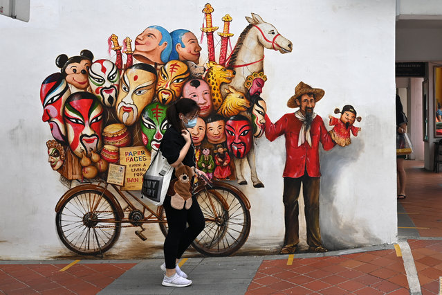 A woman walks past a mural on a wall along a street in Singapore on February 17, 2021. (Photo by Roslan Rahman/AFP Photo)