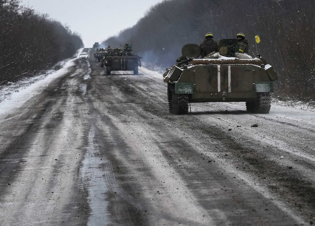 Members of the Ukrainian armed forces ride on armoured personnel carriers (APC) near Debaltseve, eastern Ukraine, February 10, 2015. (Photo by Gleb Garanich/Reuters)