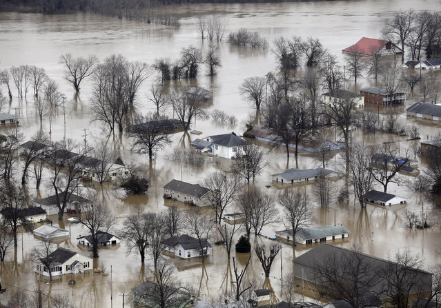In this aerial photo, homes are surrounded by floodwater, Wednesday, December 30, 2015, in Pacific, Mo. A rare winter flood threatened nearly two dozen federal levees in Missouri and Illinois on Wednesday as rivers rose, prompting evacuations in several places. (Photo by Jeff Roberson/AP Photo)