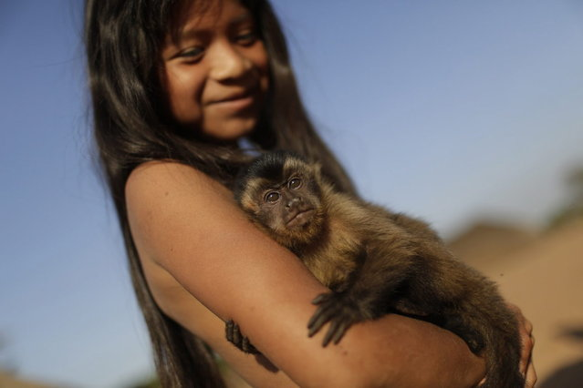 """A Waura Indian girl holds a pet monkey during this year's """"quarup"""", a ritual held over several days to honour in death a person of great importance to them, in Xingu National Park, Mato Grosso State, August 25, 2013. This year the Waura tribe honoured their late cacique (chief) Atamai, who died in 2012, for his work creating the Xingu Park and his important contribution in facilitating communication between white Brazilians and Indians. (Photo by Ueslei Marcelino/Reuters)"""