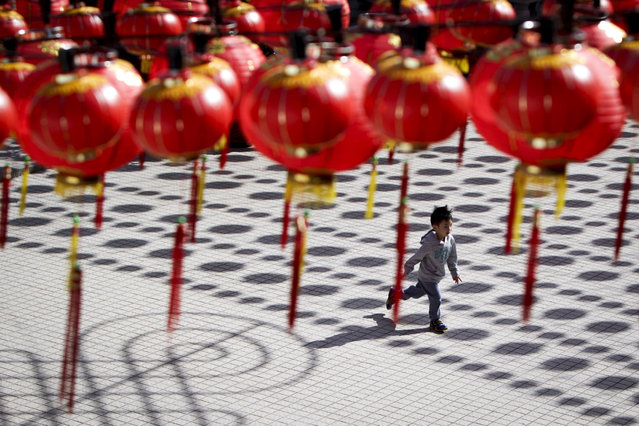A boy runs at a temple cast with shadows of traditional Chinese lantern decorations ahead of the Chinese Lunar New Year in Kuala Lumpur, Malaysia, on Tuesday, February 17, 2015. (Photo by Joshua Paul/AP Photo)