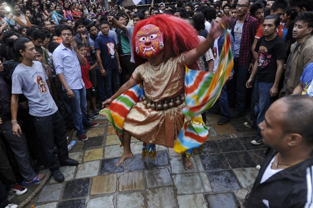 """Nepalese mask dance locally known as Lakhe dance is performed during the 4th day of Indra Jatra festival at Basantapur Durbar Square in Kathmand, Nepal, on September 19, 2013. The week-long festival celebrates """"Indra"""", the king of gods and the god of rains. (Photo by Prakash Mathema/AFP Photo)"""
