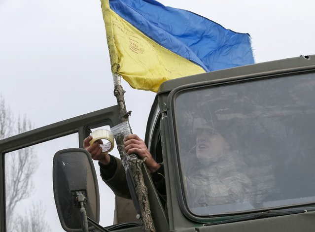 A Ukrainian serviceman who fought in Debaltseve hoists a Ukrainian national flag to his vehicle before leaving for home, near Artemivsk February 19, 2015. (Photo by Gleb Garanich/Reuters)