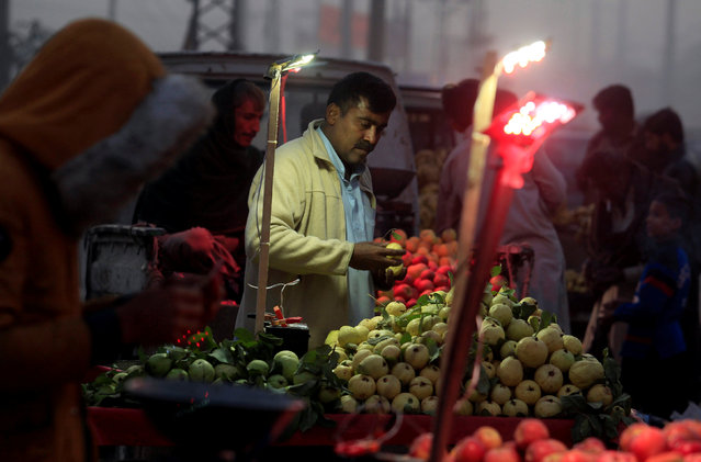 A man arranges guavas on a cart while waiting for customers along a roadside in Islamabad, Pakistan November 30, 2016. (Photo by Faisal Mahmood/Reuters)