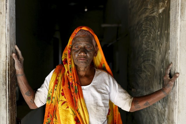 Sumitra Devi, 70, a follower of Ramnami Samaj, who has tattooed the name of the Hindu god Ram on her entire face, poses for a picture outside her house in the village of Chapora, in the eastern state of Chhattisgarh, India, November 15, 2015. (Photo by Adnan Abidi/Reuters)