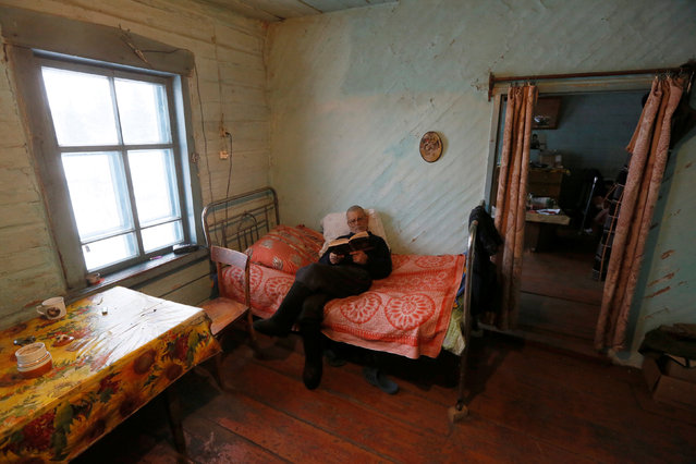 Mikhail Baburin, 66, reads a book at his house in the remote Siberian village of Mikhailovka, Krasnoyarsk region, Russia, December 5, 2016. (Photo by Ilya Naymushin/Reuters)
