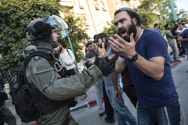 Israeli riot police tries to block a Jewish right-wing man as clashes erupted between Arabs, police and Jews, in the mixed town of Lod, central Israel, Wednesday, May 12, 2021. As rockets from Gaza streaked overhead, Arabs and Jews fought each other on the streets below. Rioters torched vehicles, a restaurant and a synagogue in one of the worst spasms of communal violence that Israel has seen in years. (Photo by Heidi Levine/AP Photo)