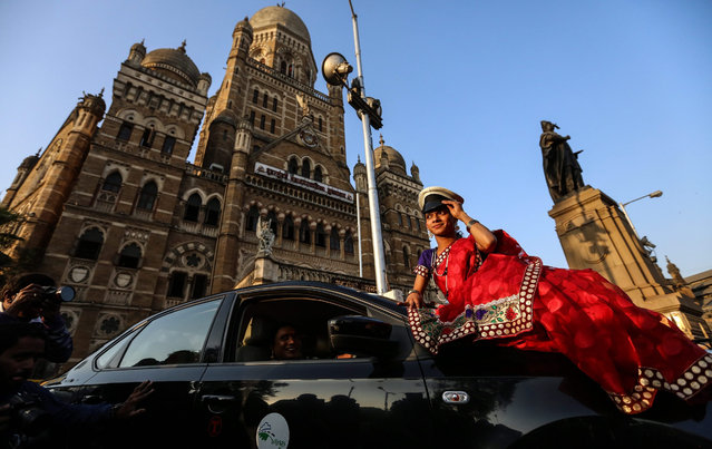 Indian transgender drivers Sanjeevani Chavan (R) and Sarika Pawar (L) pose for photographs with the Wings travels taxi outside the Chhatrapati Shivaji Terminus railway station, in Mumbai, India, 20 January 2016. (Photo by Divyakant Solanki/EPA)
