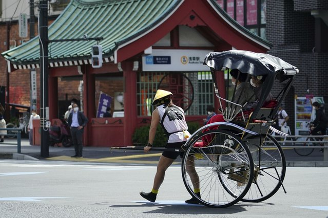 A rickshaw puller carries tourists near Sensoji Buddhist temple at Tokyo's Asakusa district in Tokyo on March 31, 2021. The Japanese economy contracted at an annual rate of 5.1% in January-March, slammed by a plunge in spending over the coronavirus pandemic, according to government data released Tuesday, May 18, 2021. (Photo by Eugene Hoshiko/AP Photo)