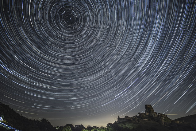 Satellites, planes and comets transit across the night sky under stars that appear to rotate above Corfe Castle on August 12, 2016 in Corfe Castle, United Kingdom. The Perseids meteor shower occurs every year when the Earth passes through the cloud of debris left by Comet Swift-Tuttle, and appear to radiate from the constellation Perseus in the north eastern sky. (Photo by Dan Kitwood/Getty Images)