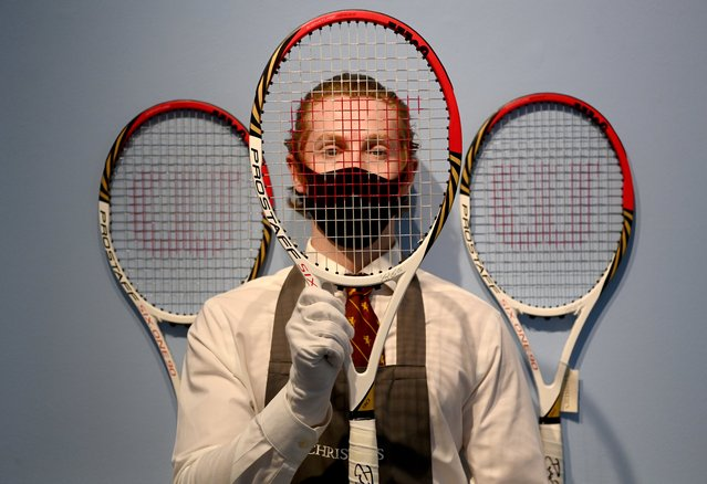 """A Christie's employee poses with Swiss tennis Roger Federer's racket used at the London Olympics 2012 at the Christie's auction house, in London, Britain, 21 June 2021. An online auction of parts of the Swiss tennis player's equipment from various international tennis tournaments will take place from 23 June until 14 July to raise funds for the """"Roger Federer Foundation"""". (Photo by Facundo Arrizabalaga/EPA/EFE)"""