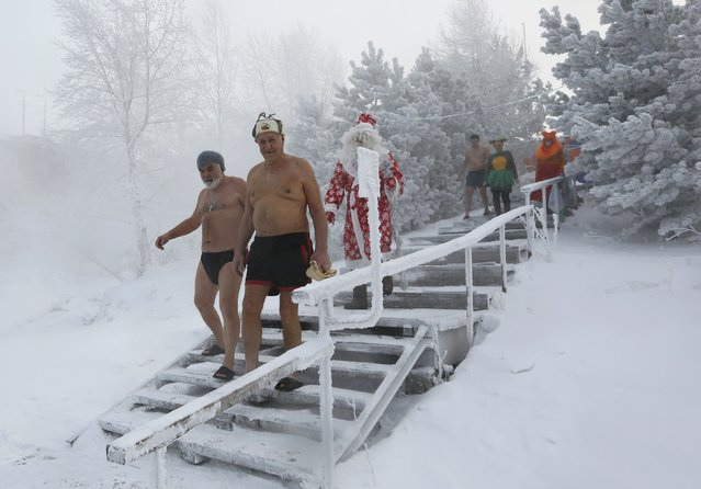 Members of the Cryophile amateurs winter swimmers club, accompanied by a man dressed as Ded Moroz, the Russian equivalent of Santa Claus, and other fancy characters, walk before taking a bath in the icy waters of the Yenisei River during the celebrations for the upcoming Christmas and New Year, with the air temperature at about minus 34 degrees Celsius (minus 29.2 degrees Fahrenheit), in Krasnoyarsk, Russia, December 24, 2016. (Photo by Ilya Naymushin/Reuters)