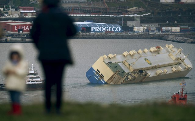 People observe the stricken cargo ship Modern Express from a hilltop as it is towed into the port of Bilbao, northern Spain, February 3, 2016. (Photo by Vincent West/Reuters)