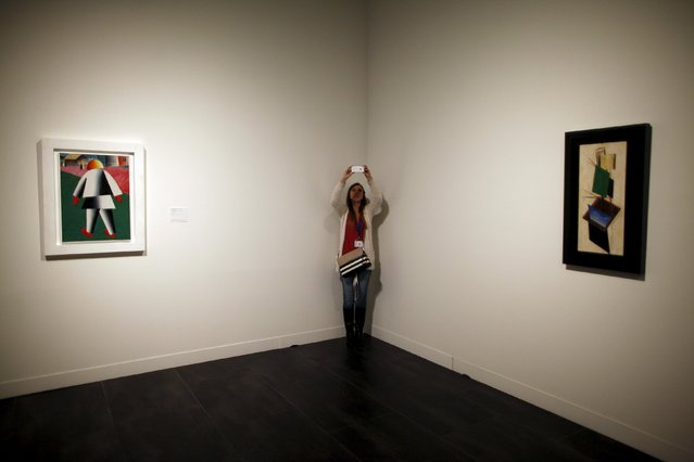 """A woman takes pictures in between """"Composition with white border"""" (L) and """"Construction"""" by Russian-born artists Kasimir Malevich and Alexander Rodchenko during an international press tour of the Malaga branch of the State Museum of Russian Art of St Petersburg, a day before its inauguration in Malaga, southern Spain March 24, 2015. (Photo by Jon Nazca/Reuters)"""