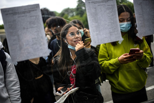 Students react as they check the results of the baccalaureat exam (high school graduation exam) at the Rodin high school in Paris on July 6, 2021. (Photo by Christophe Archambault/AFP Photo)