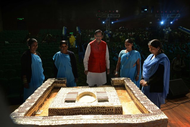 Indian social reform activist and founder of Sulabh Sanitation Bindeshwar Pathak (C) presents a 250-kilogram cake in the form of a squat toilet during a function to mark World Toilet Day In New Delhi on November 19, 2013. According to a 2011 census, some 131 million households in India have no latrine in their premises, with eight million using public facilities and 123 million defecating in the open. (Photo by Sajjad Hussain/AFP Photo)