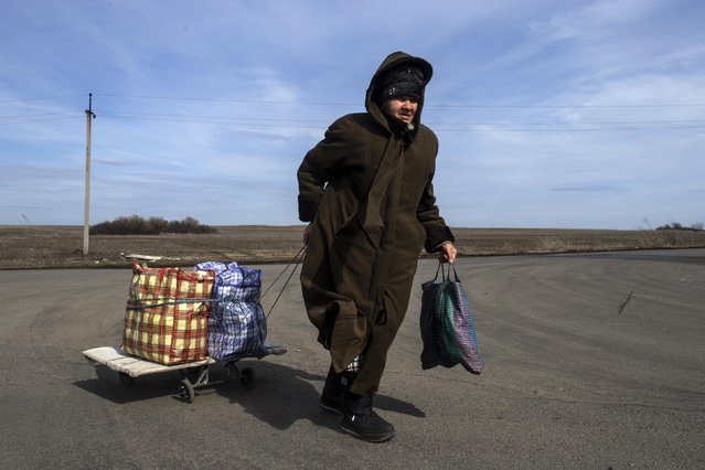 A woman pulls her bags as she is about to cross the Uspenka border crossing between Ukraine and Russia, southeast from Donetsk, March 15, 2015. (Photo by Marko Djurica/Reuters)