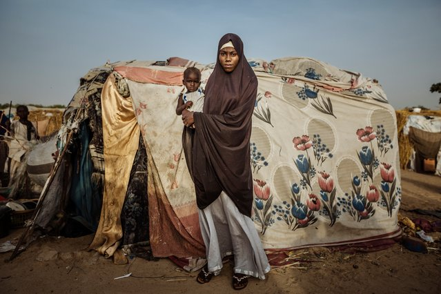 A woman and her child pose outside of their makeshift home built from a collection of fabrics inside the Farm Centre IDPs camp in Maiduguri, Nigeria. (Photo by Muse Mohammed/IOM)