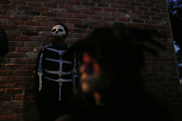 A member of the North Side Skull & Bone Gang stands against a wall waiting to continue the parade during the wake up call for Mardi Gras, Tuesday, February 9, 2016, in New Orleans. (Photo by Brynn Anderson/AP Photo)