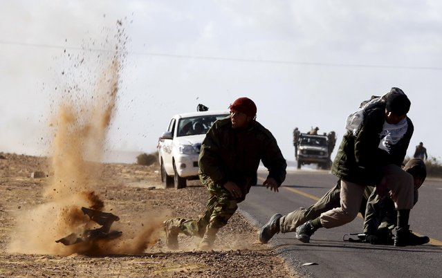 Rebel fighters jump away from shrapnel during heavy shelling by forces loyal to Libyan leader Muammar Gaddafi near Bin Jawad, March 6, 2011. (Photo by Goran Tomasevic/Reuters)