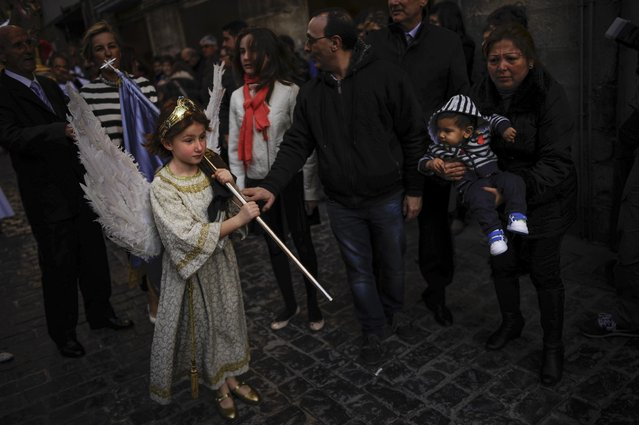 """Eight-year-old Alba Oroz, waering an angel costume takes part during the Easter Sunday ceremony """"Descent of the Angel"""", during Holy Week in the small town of Tudela, northern Spain, Sunday, April 5, 2015. (Photo by Alvaro Barrientos/AP Photo)"""