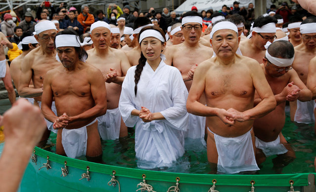 People wearing loin cloths pray as they bathe in ice-cold water outside the Teppozu Inari shrine in Tokyo, Japan, January 8, 2017. (Photo by Toru Hanai/Reuters)