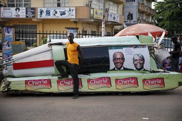 Durojaye Obasanjo stands next to a locally constructed automative jet, with a banner showing photographs of Nigeria's President-elect Muhammadu Buhari and his Vice President-elect Yemi Osinbajo along a road in Ikeja district of Lagos April 6, 2015. (Photo by Akintunde Akinleye/Reuters)