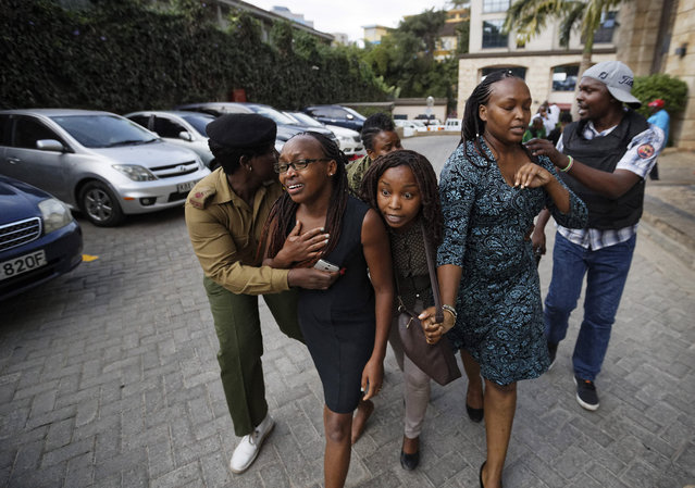 Civilians flee the scene at a hotel complex in Nairobi, Kenya Tuesday, January 15, 2019. An upscale hotel complex in Kenya's capital came under attack on Tuesday, with a blast and heavy gunfire. The al-Shabab extremist group based in neighboring Somalia claimed responsibility and said its members were still fighting inside. (Photo by Ben Curtis/AP Photo)