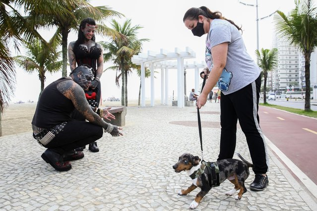 Brazilian tattoo artist Michel Praddo, also known as Diabao or Human Satan, and his wife Carol Praddo, known as Mulher Demonia or Demon Woman, play with a dog at the beach shore in Praia Grande, Brazil on August 18, 2021. (Photo by Carla Carniel/Reuters)