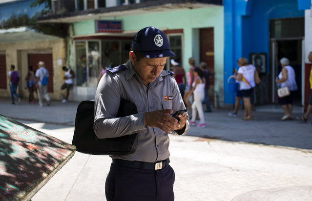 A policeman gets connected to the internet using his phone in Havana, Cuba, Wednesday, August 22, 2018. (Photo by Desmond Boylan/AP Photo)