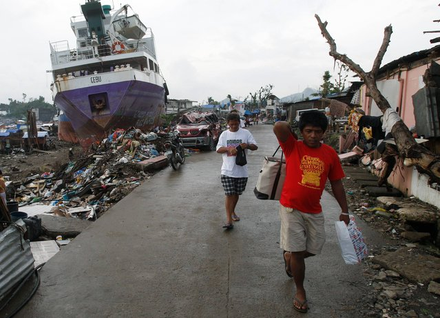 Typhoon survivors walk near shipping vessels that remain grounded after being washed ashore during Typhoon Haiyan in Tacloban, Philippines, Monday, December 23, 2013. Villages in the central Philippines were flattened by Haiyan's ferocious winds and the tsunami-like storm surge that damaged or swept away more than a million homes. Haiyan, one of the most powerful storms on record, hit the country's eastern seaboard on November 8. (Photo by Achmad Ibrahim/AP Photo)