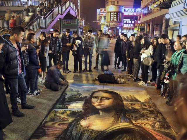 In this photo taken Friday April 10, 2015,  Cong Langui, 53, creates a six-square-meter chalking drawing of Leonardo da Vinci's masterpiece, the Mona Lisa, also known as La Gioconda, on the street of Jinhua in east China's Zhejiang province. Cong who lost his left leg to a bone tumor in his youth draws to earn a living on the streets. (Photo by AP Photo/Stringer)
