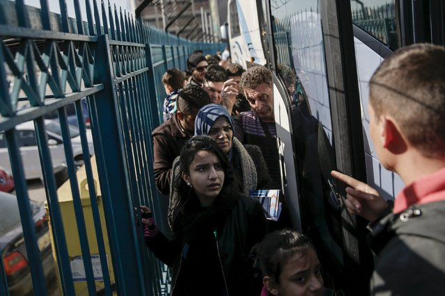 Syrian and Iraqi refugees prepare to board a bus heading to the Greek-Macedonian border, following their arrival aboard the Blue Star 1 passenger ship from the islands of Lesbos and Chios, at the port of Piraeus, near Athens, Greece, February 23, 2016. (Photo by Alkis Konstantinidis/Reuters)