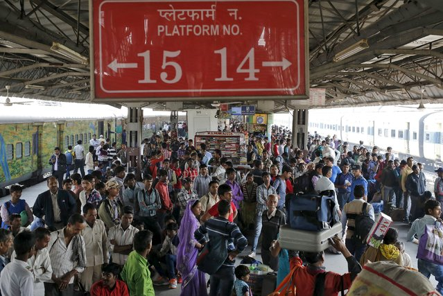 Passengers wait to board a train at a railway station in New Delhi, India, February 25, 2016. India's state-owned railway said on Thursday it planned to cut costs and generate new sources of revenue next year to offset a big rise in its wage bill and help keep an ambitious modernisation plan on track on track. (Photo by Anindito Mukherjee/Reuters)