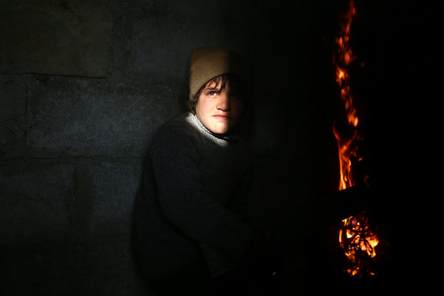 A boy stands near a fire in the rebel held besieged Douma neighbourhood of Damascus, Syria January 17, 2017. (Photo by Bassam Khabieh/Reuters)