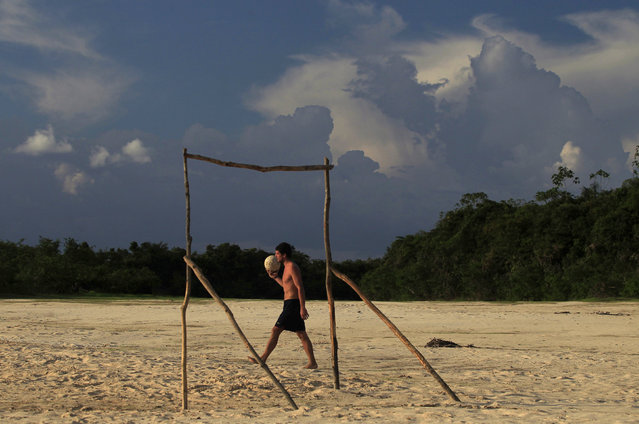 A man holds a soccer ball at a beach by the shore of Nanay river in Iquitos, Peru, September 7, 2011. (Photo by Pilar Olivares/Reuters)